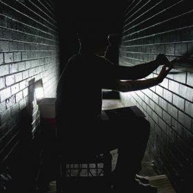 man in a dark tunnel-like room