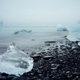 """chucks of ice on a pebbled wintery beach - imagery for """"Considerations"""" by Laurinda Lind"""