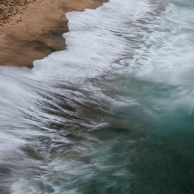 """aerial view of ocean waves at the shore - imagery for """"Paved with Good Intentions"""" by Sophie van Llewyn"""