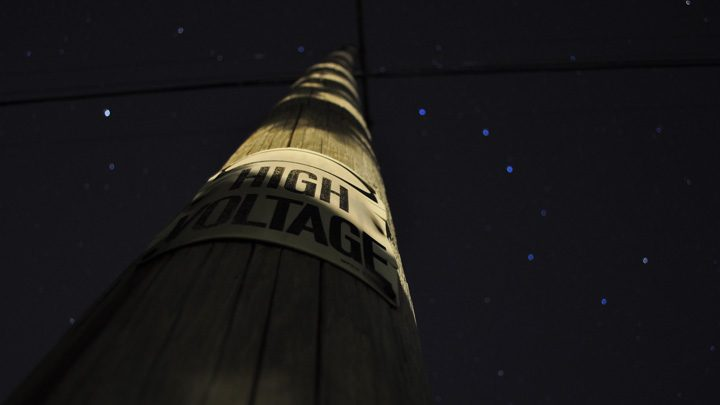 """High voltage sign on a pole in the dark - imagery for """"Something About Bursting"""" by Lauren Suchenski"""