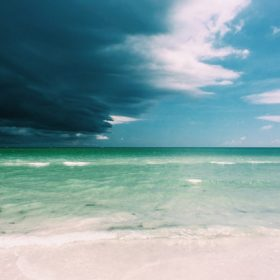 """A pristine beach with darkening sky - imagery for """"Why We Went to Florida"""" by Glen Sorestad"""