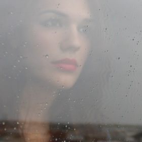 woman looking out the window in the rain